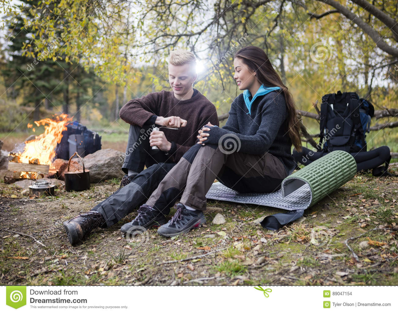 Woman With Man Grinding Coffee During Camping In Forest