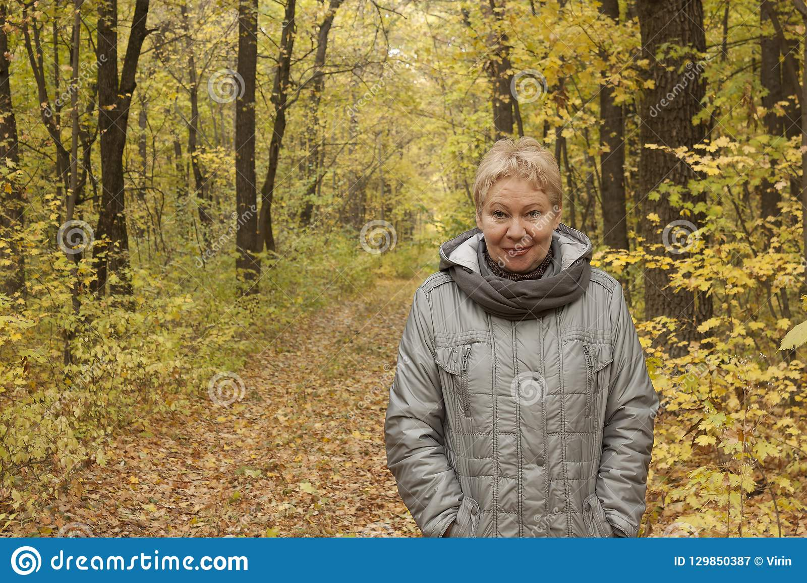 A Woman Of Mature Age In The Forest With Yellow Leaves Stock Image