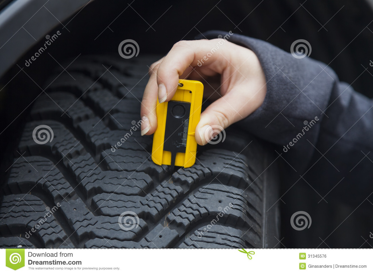 woman measures tire tread of a car tire stock photo image 31345576. Black Bedroom Furniture Sets. Home Design Ideas