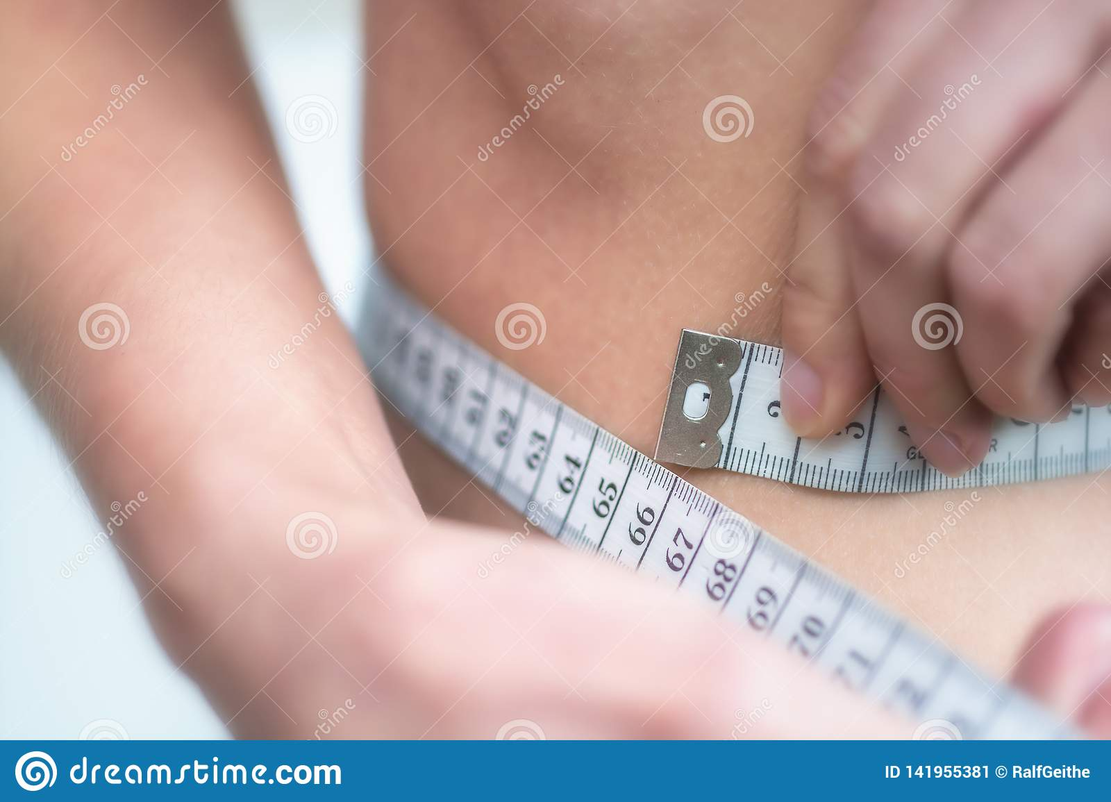 Woman measures very thin waist with measuring tape
