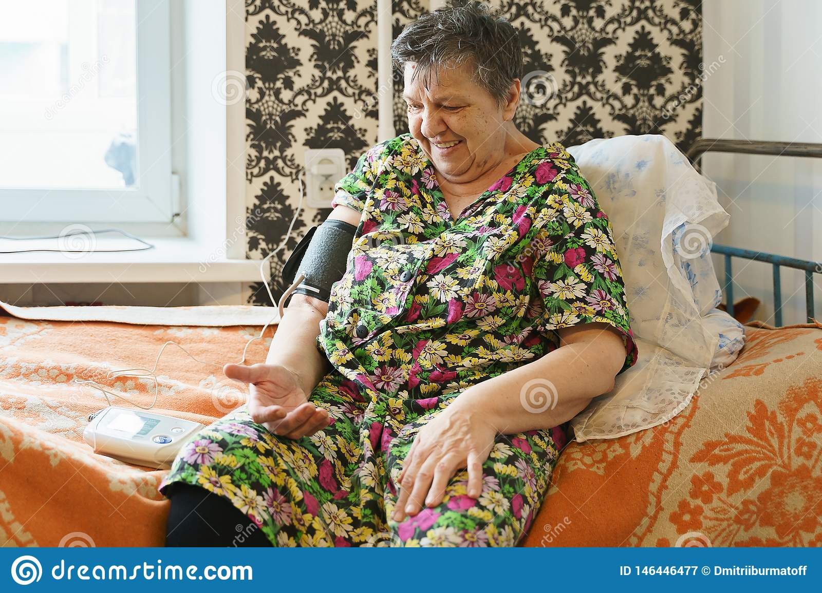 Woman measuring blood pressure with tonometer herself