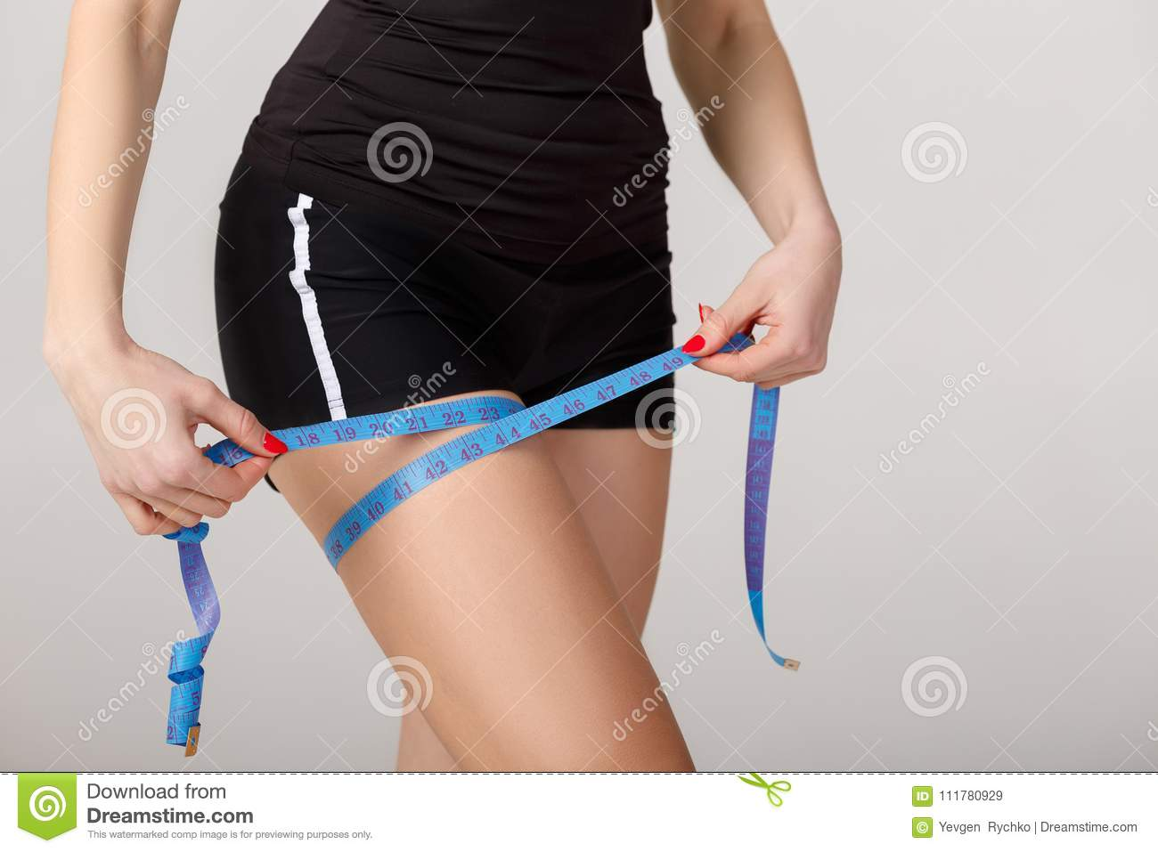 Woman measuring hip with measuring tape