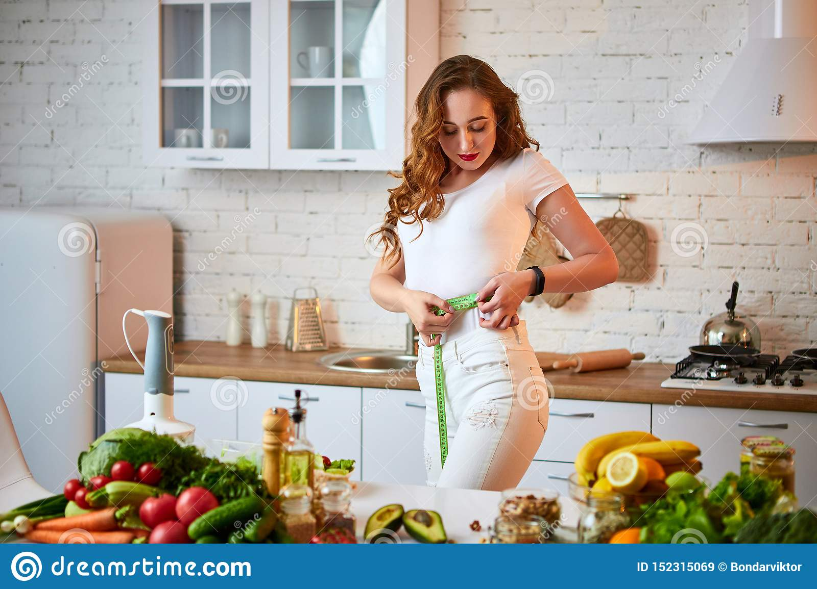Woman measuring perfect shape of beautiful waist with green tape centimeter. Healthy Lifestyle and Eating. Health, Beauty, Diet