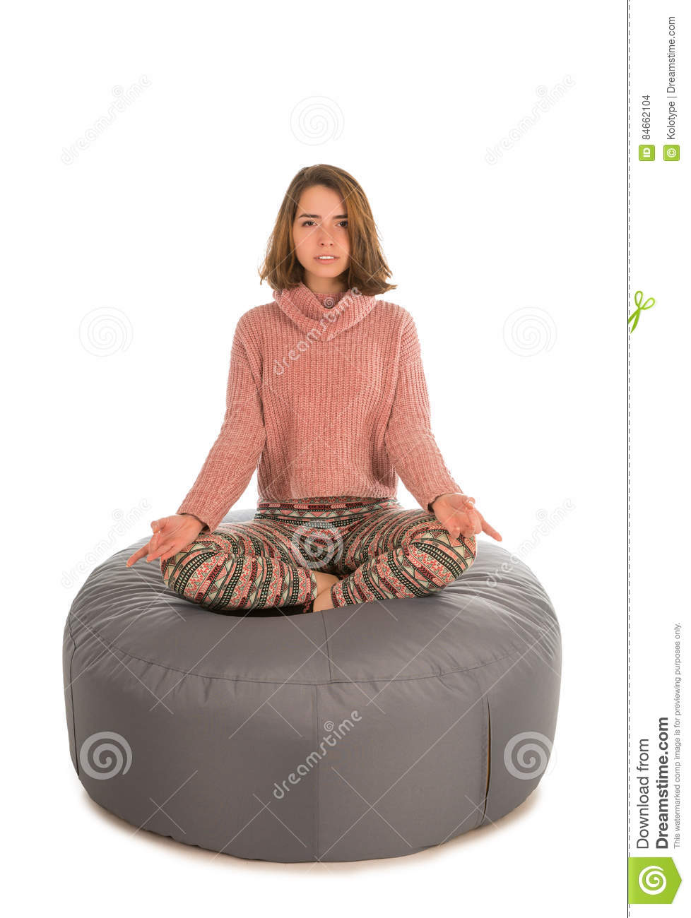Woman Meditates While Sitting In The Lotus Position On ...