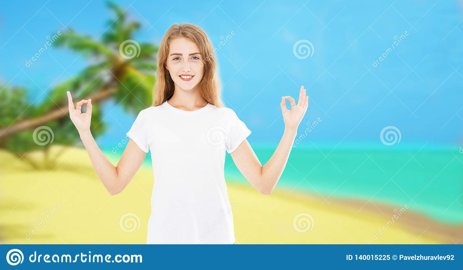 Woman meditating on tropical palm beach hands up. Beautiful female model enjoying sun in worship and meditation zen. Islands