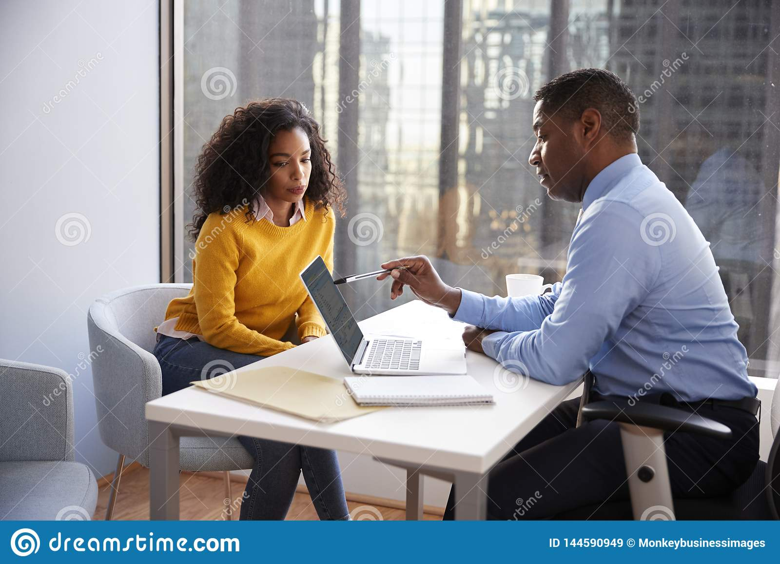 Woman Meeting With Male Financial Advisor Relationship Counsellor In Office