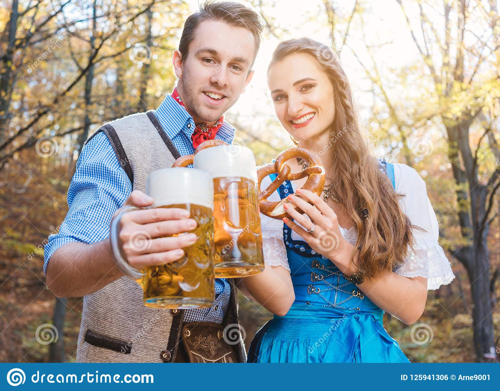 Woman and man in Bavarian Tracht drinking beer