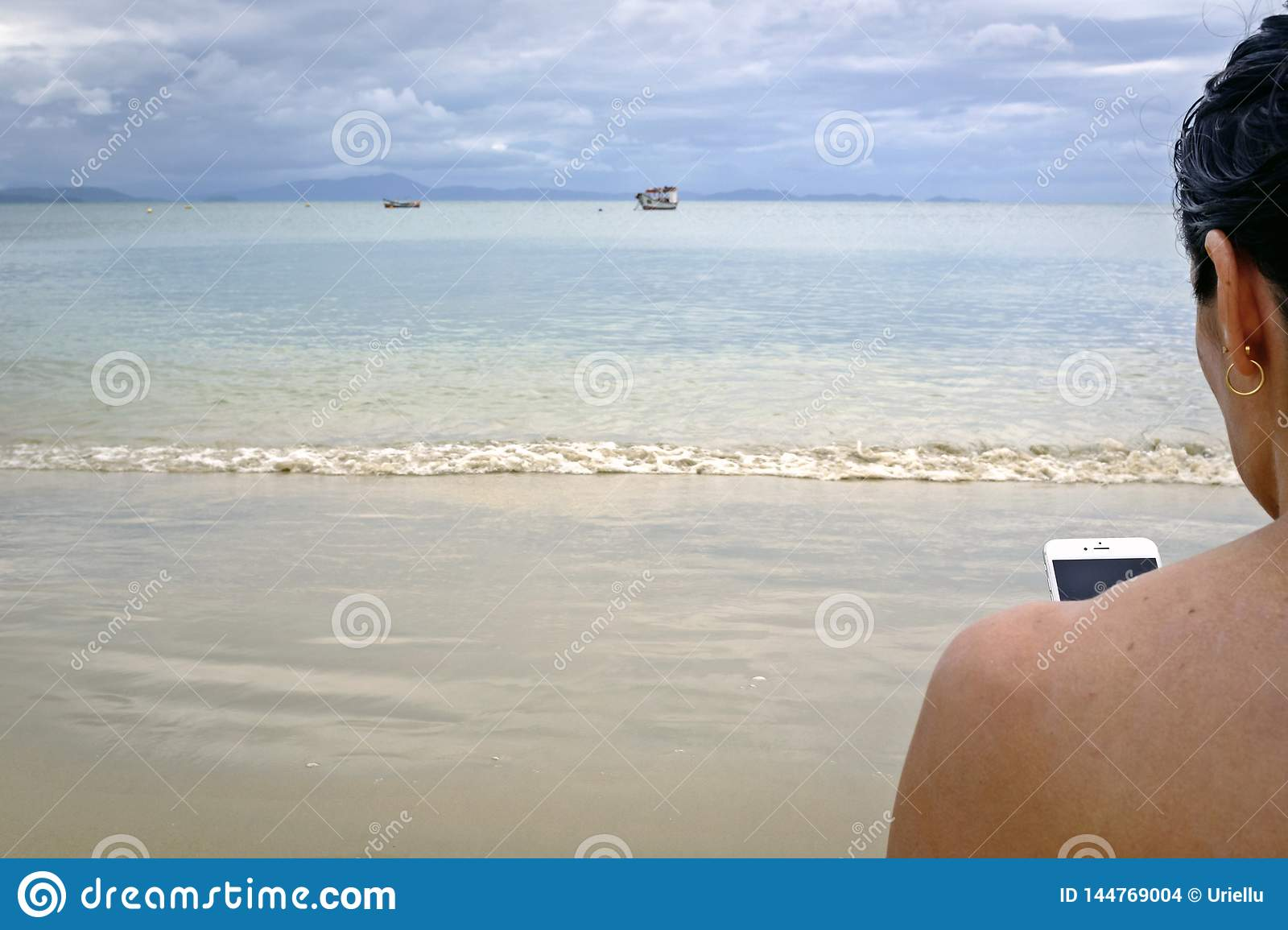 Woman with mobile on the beach