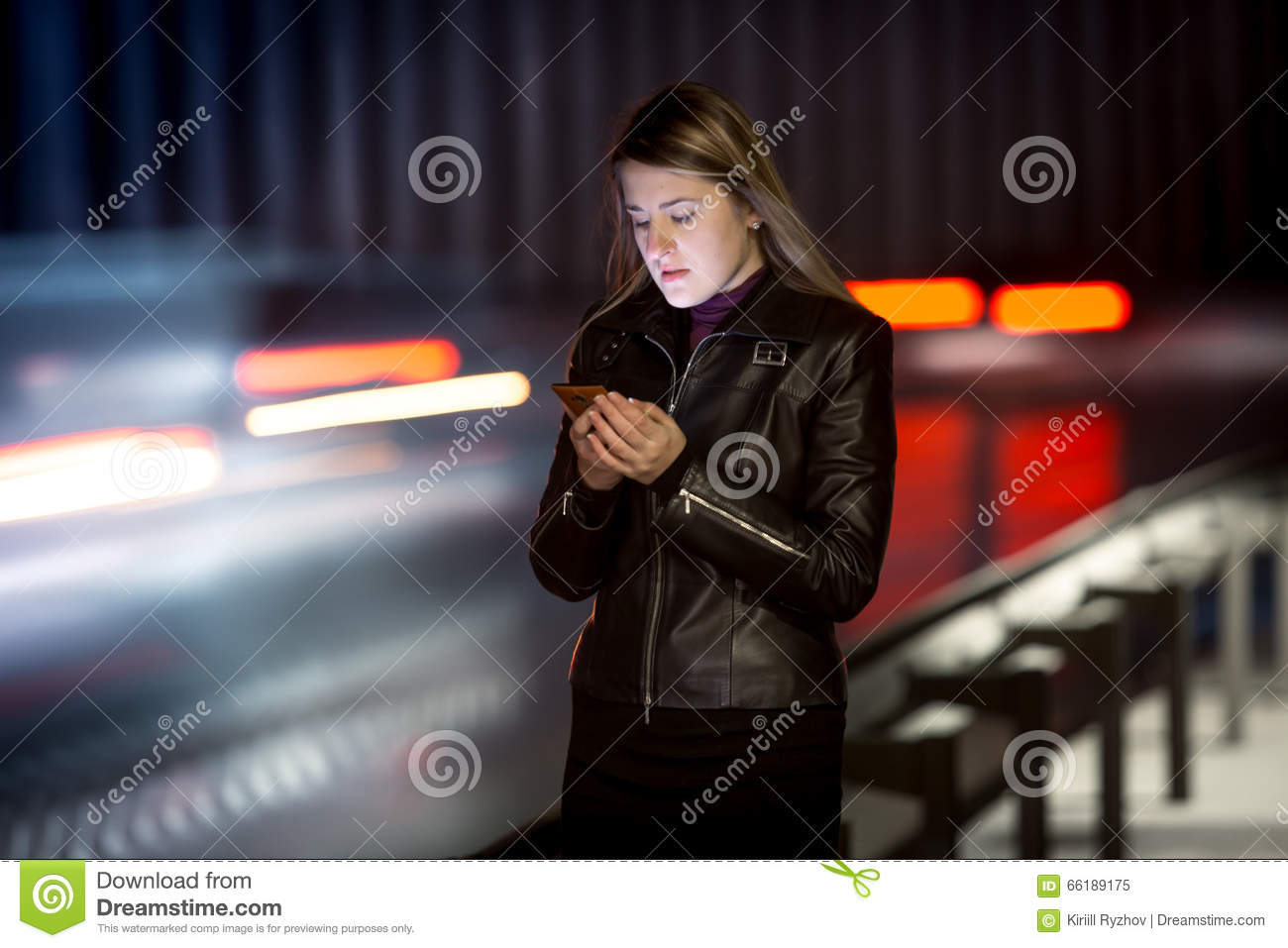 Woman with mobile phone walking at night next to highway
