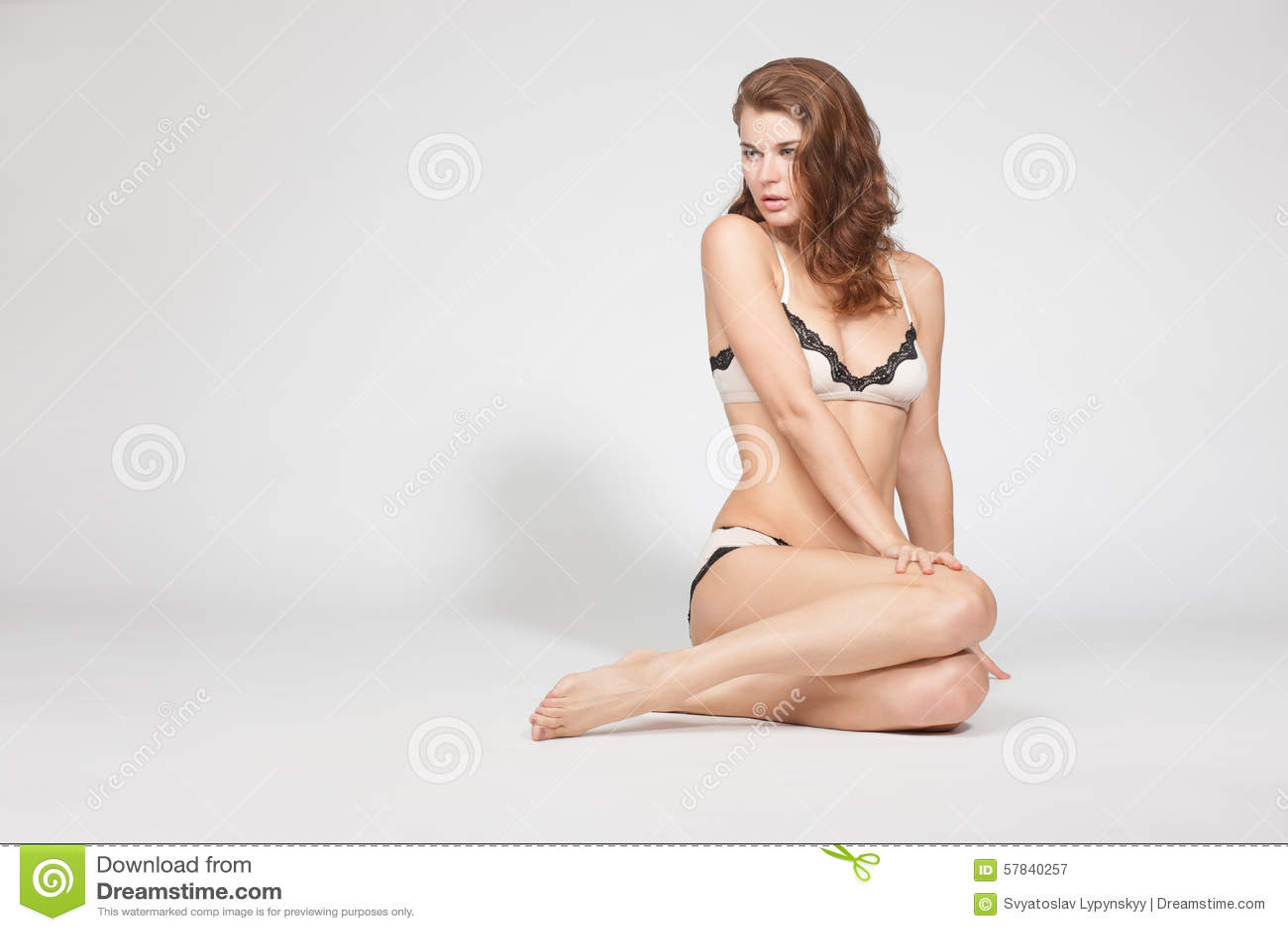 9da6f9f7bcfb Portrait of slim and slender woman model in bikini. Pretty woman in white underwear  sitting on the floor, studio shot.