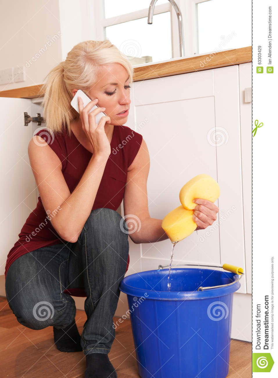 woman-mopping-up-leaking-sink-phone-to-emergency-plumber-mops-63303429.jpg