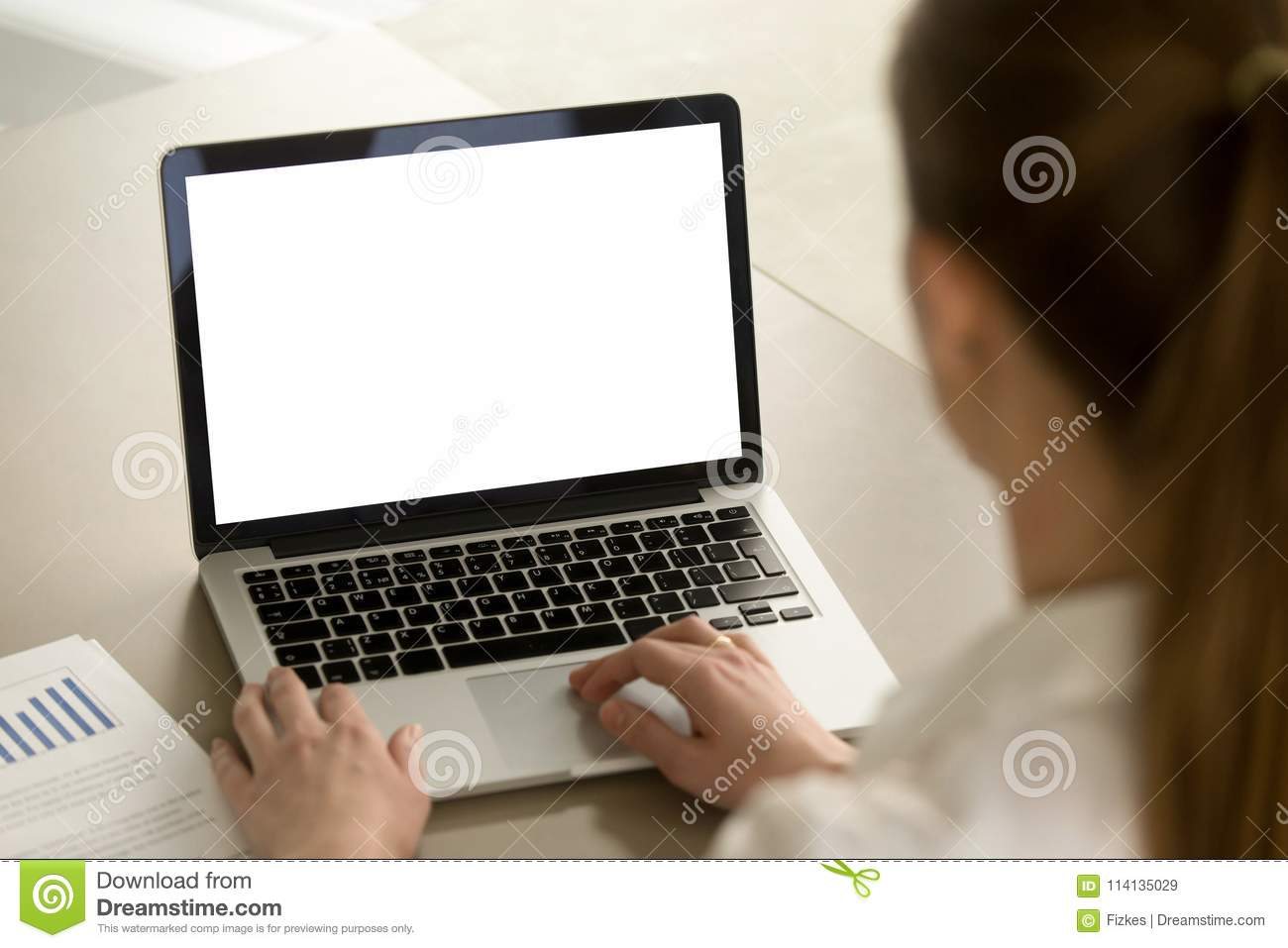 Woman in office working on laptop with mockup blank screen.