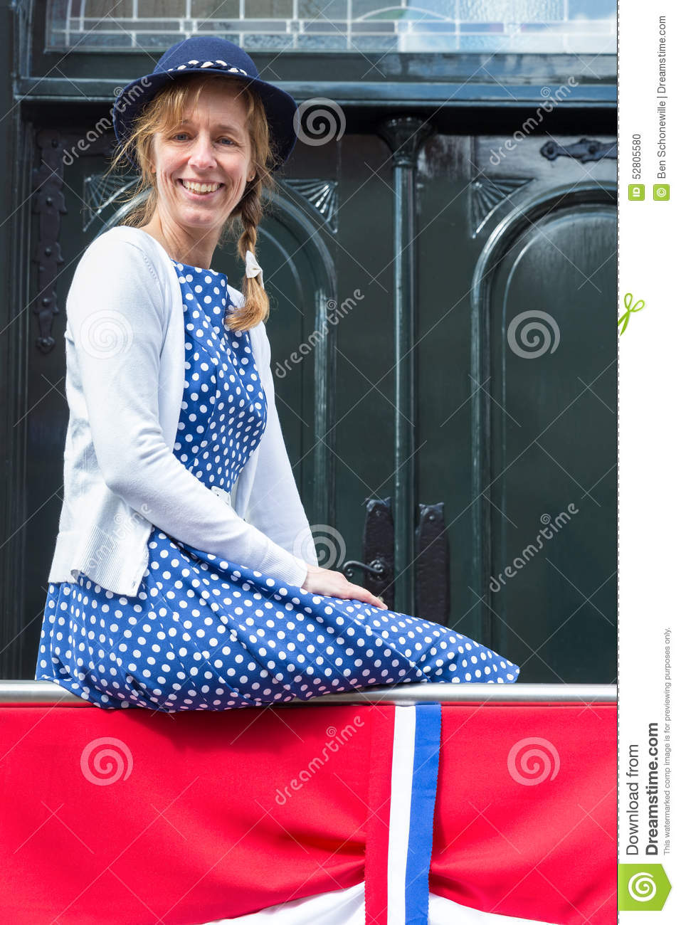 Woman in old-fashioned clothes with dutch flag