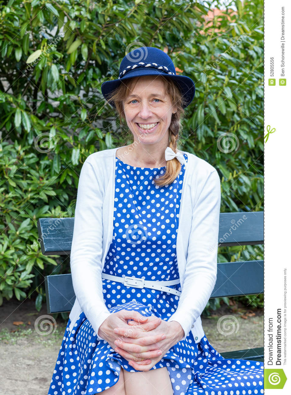 Woman in old-fashioned clothes sitting on bench in park