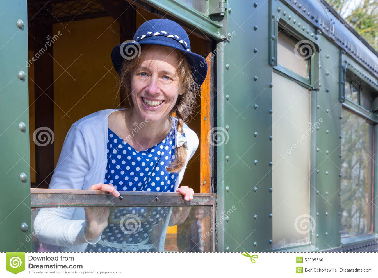 Woman in old-fashioned clothes in window of steam train