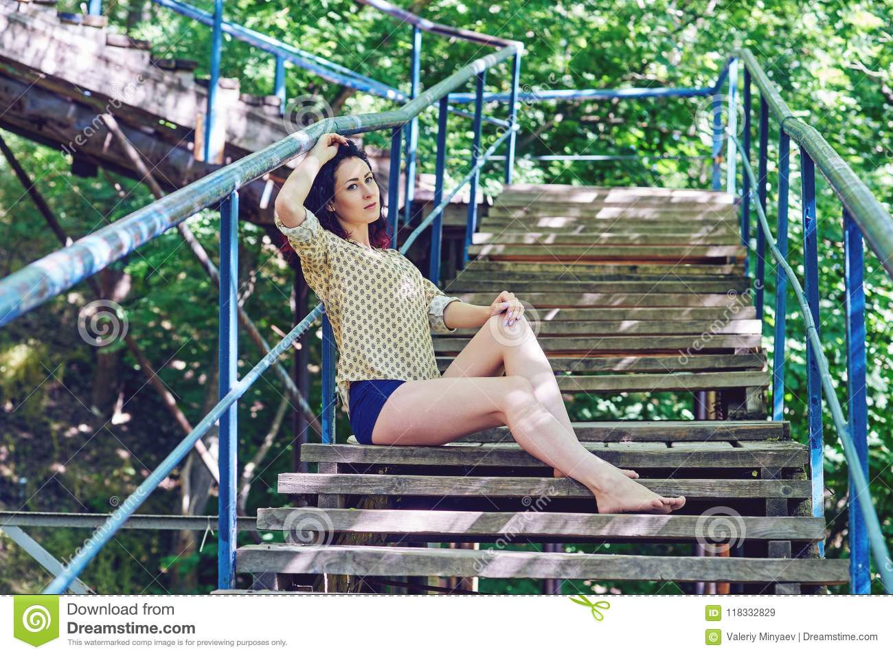 A Woman On An Old Wooden Staircase In The City Park Stock