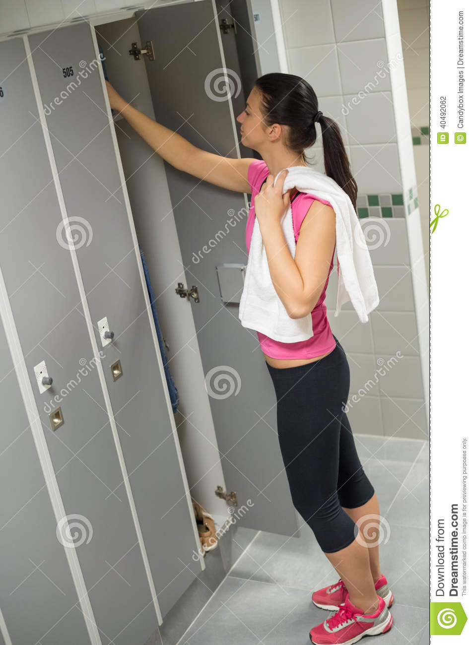 Woman opening locker at gym stock photo cartoondealer