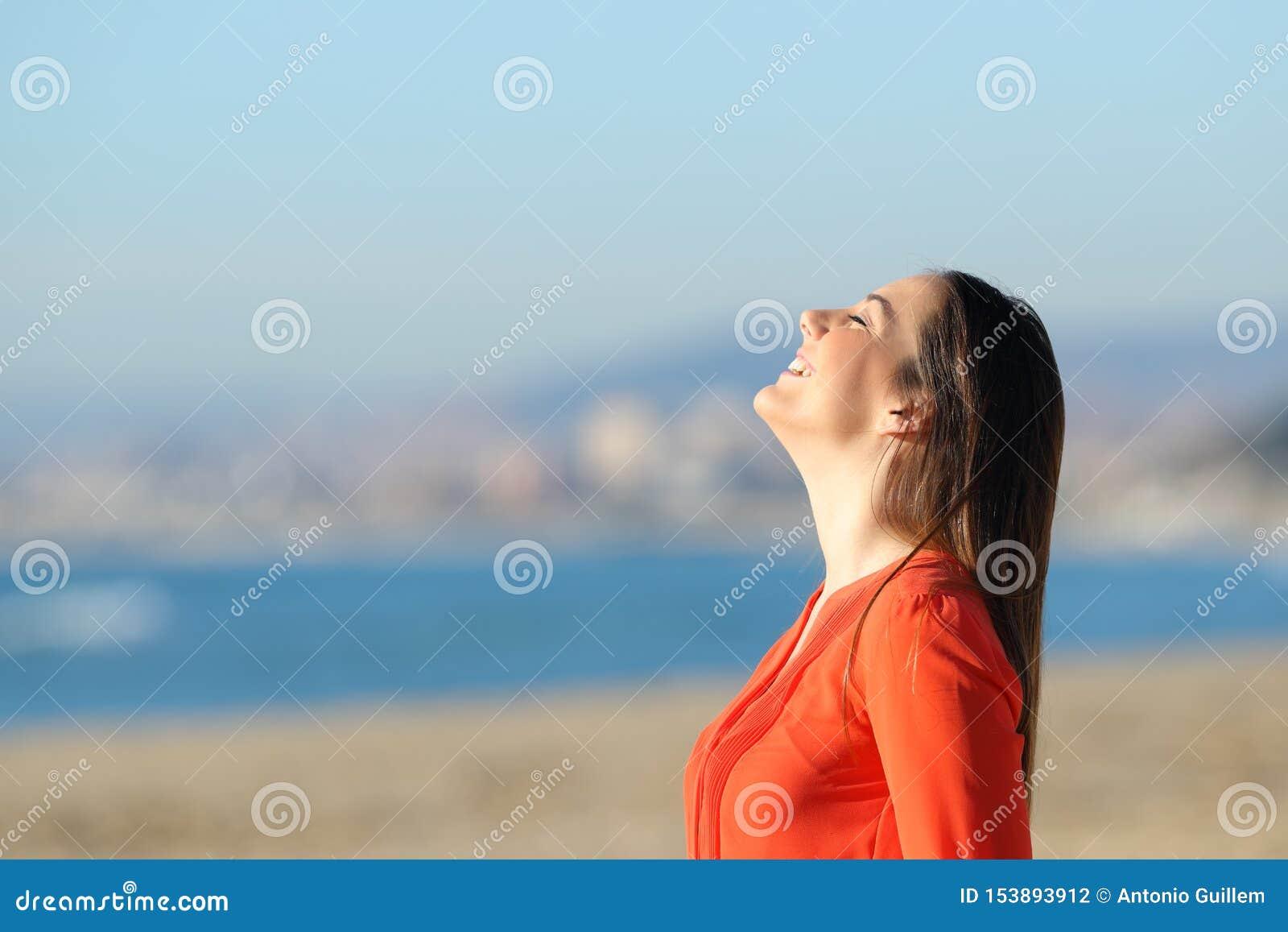 Woman in orange breathing fresh air on the beach