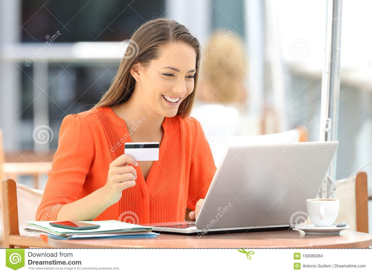 Woman in orange paying on line with a credit card