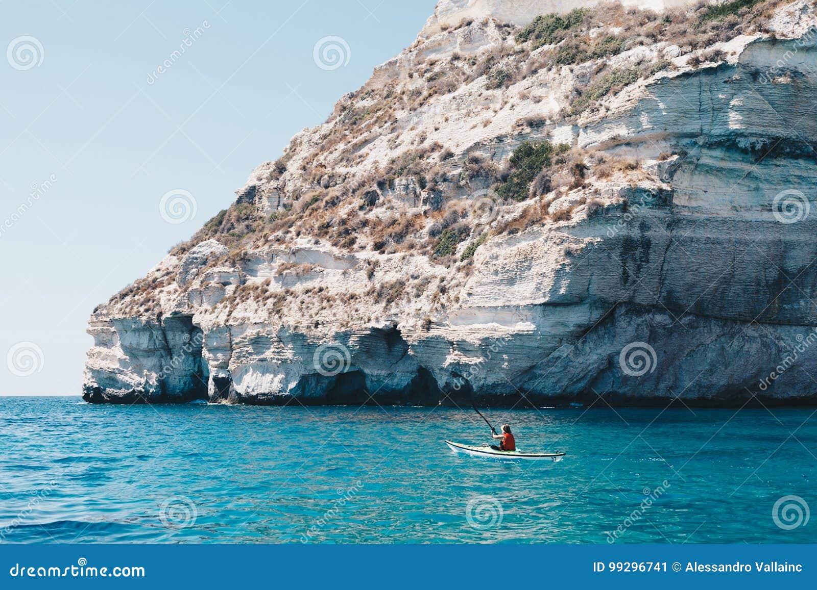 Woman paddles kayak in a calm sea in Sardinia Italy