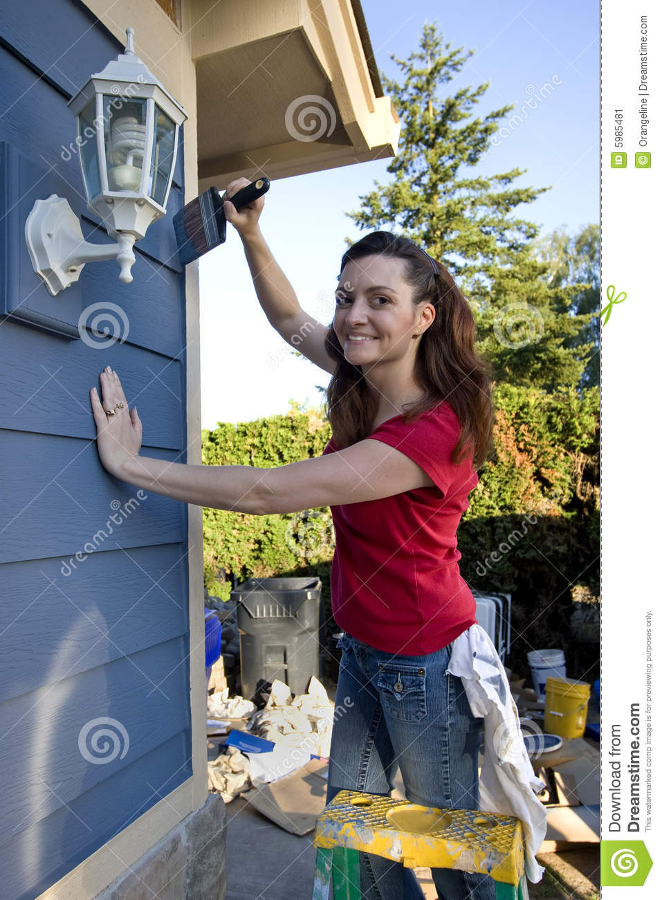 Woman Painting A Blue House Vertical Stock Image Image