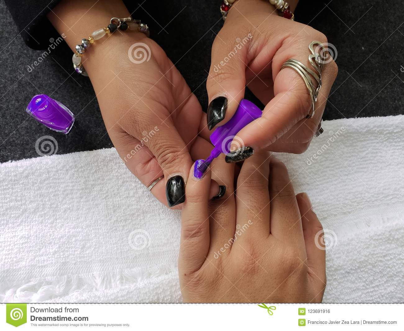 Woman Painting The Fingernails Of Another Woman With Purple Nail ...