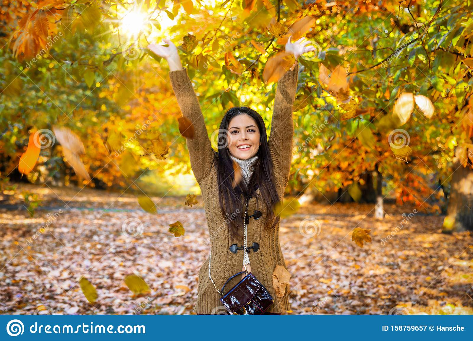 Woman in a park during golden autumn time