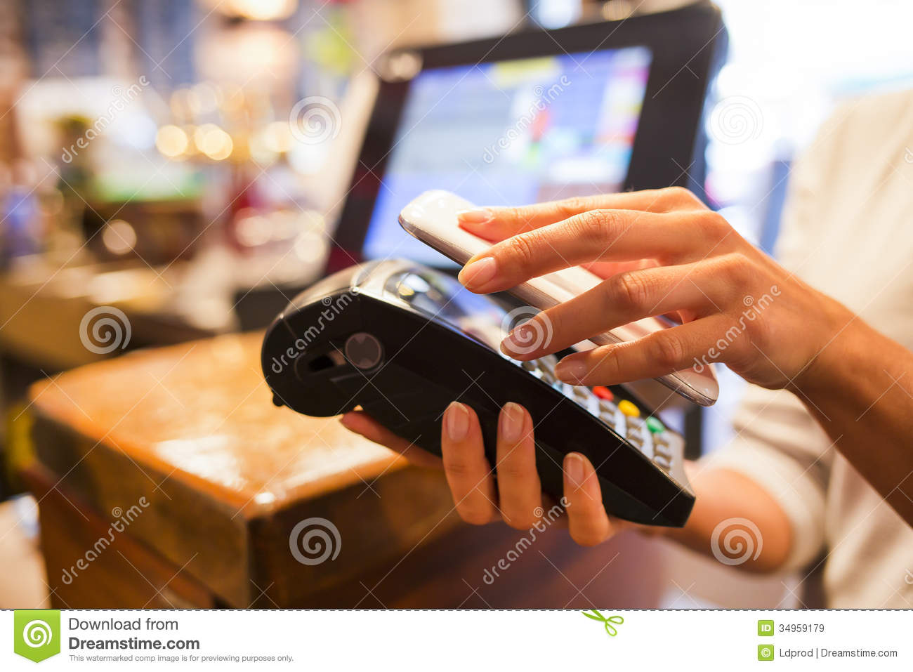 Woman paying with nfc technology on mobile phone for Onlineshop fur mobel