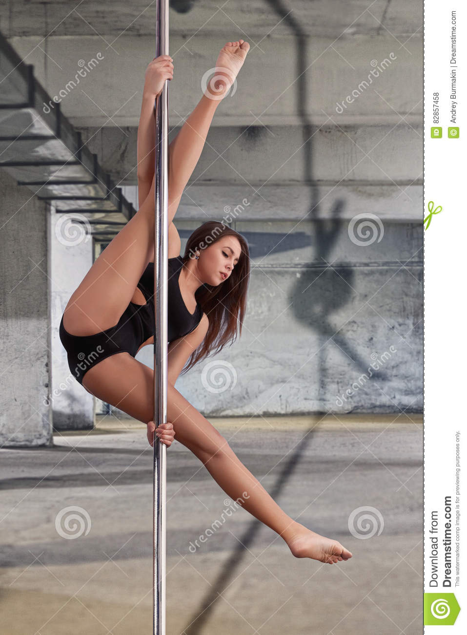 woman performing pole dance shot with wall background stock photo