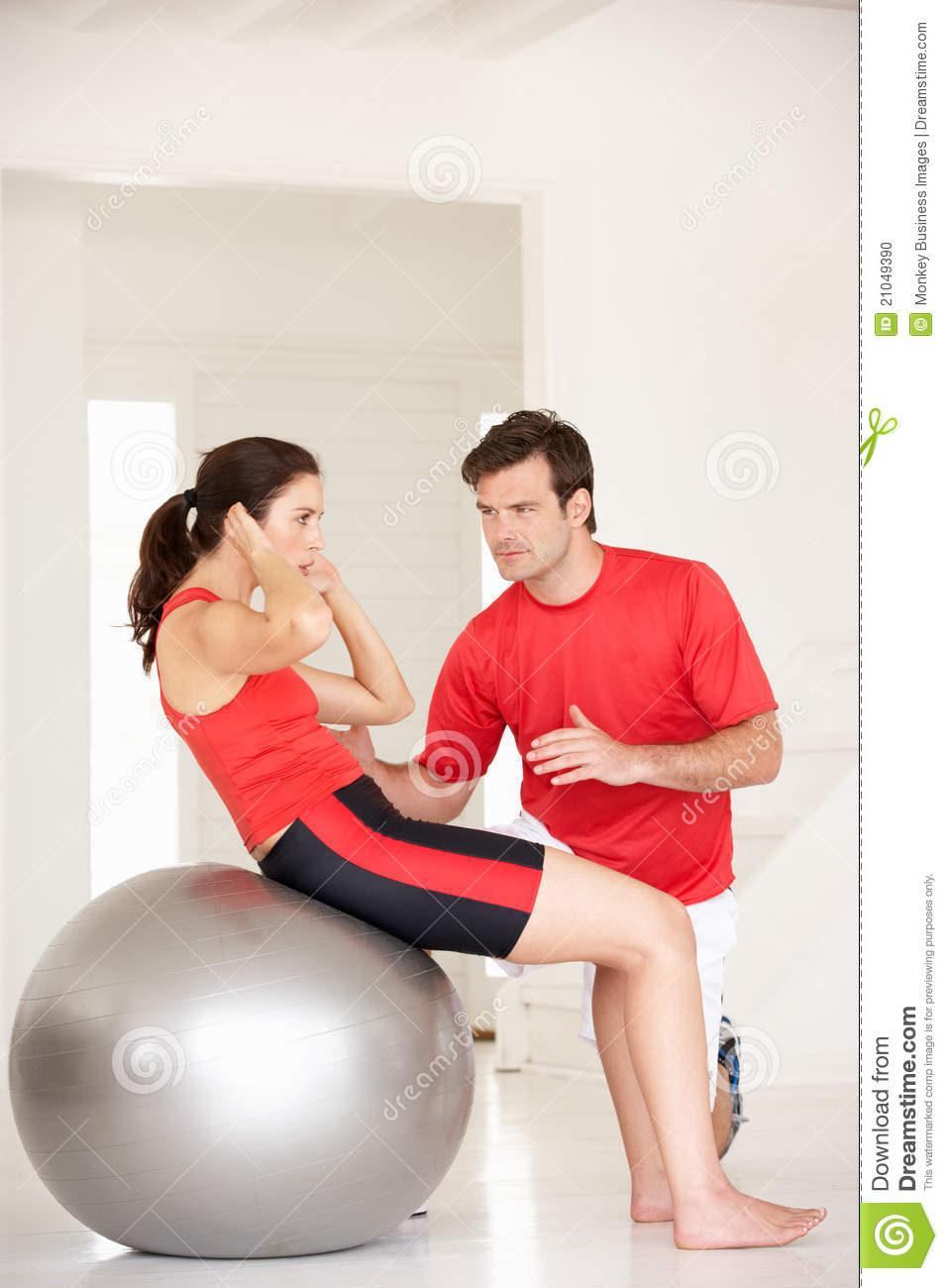 Woman with personal trainer in home gym stock photo