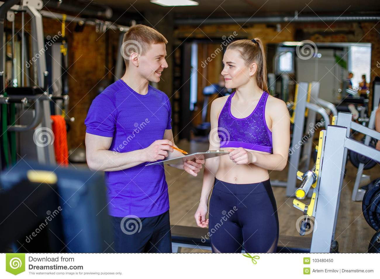 Woman with personal trainer preparing training plan in gym.