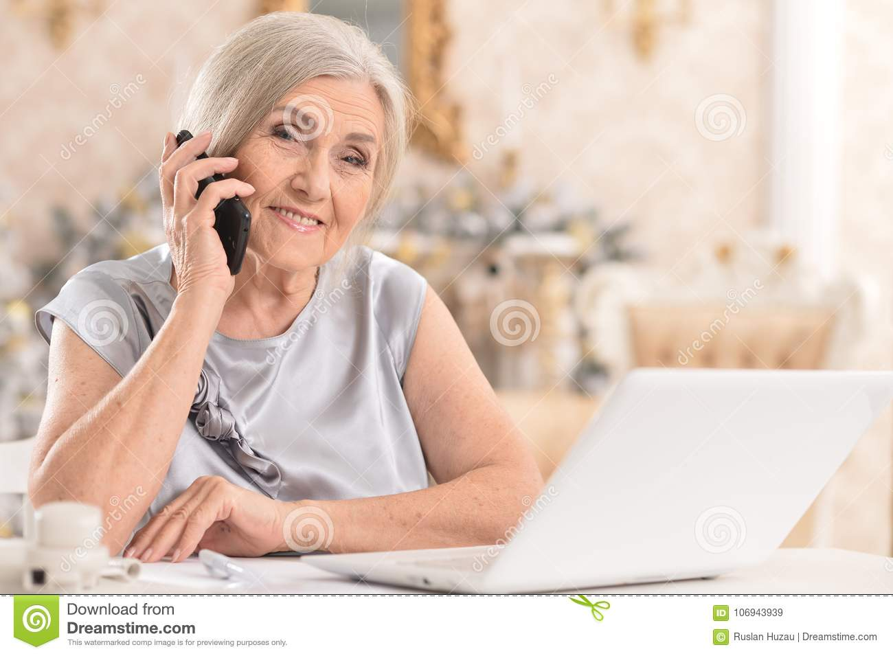 woman with phone using laptop