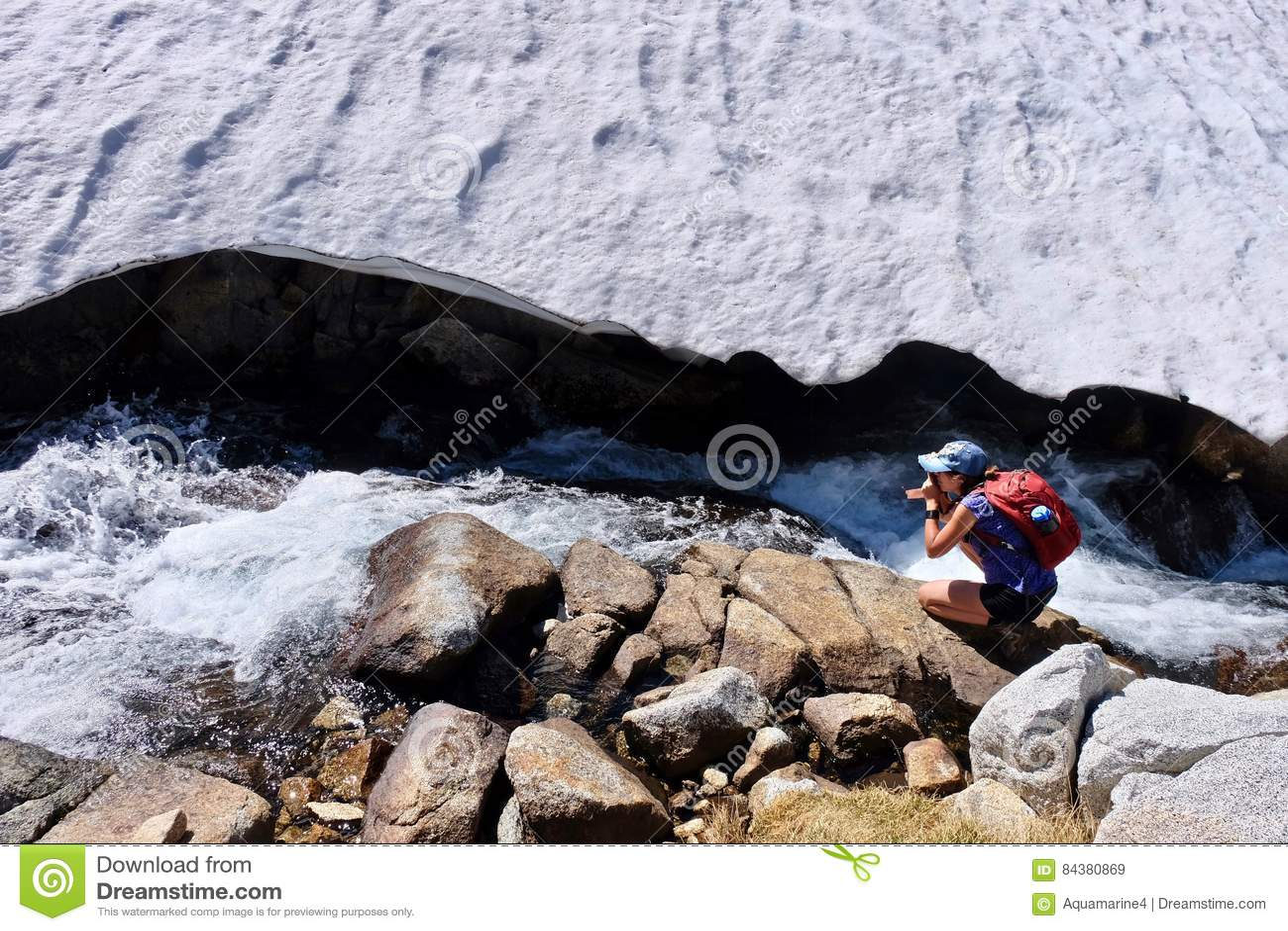 Woman photographer by alpine creek.