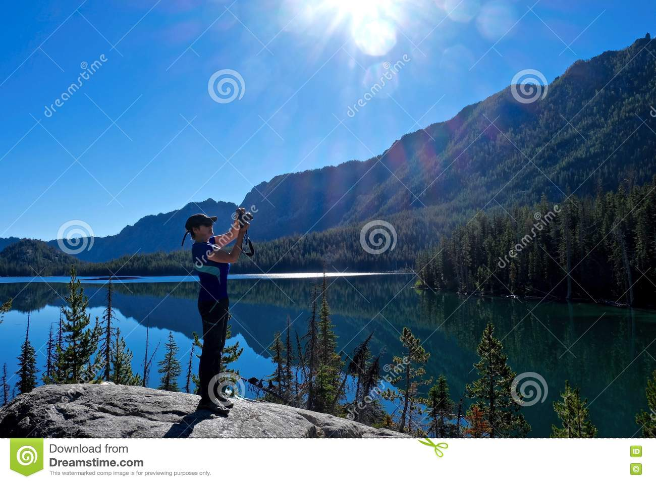 Woman photographer by alpine lake with reflection in calm water.