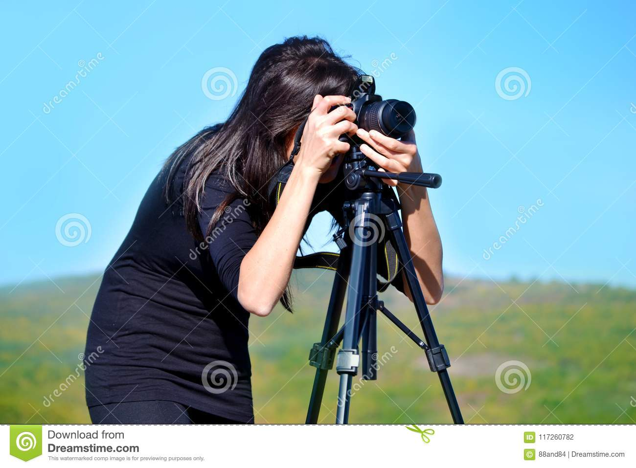 Woman Photographer Taking Photos with Digital Camera and Tripod