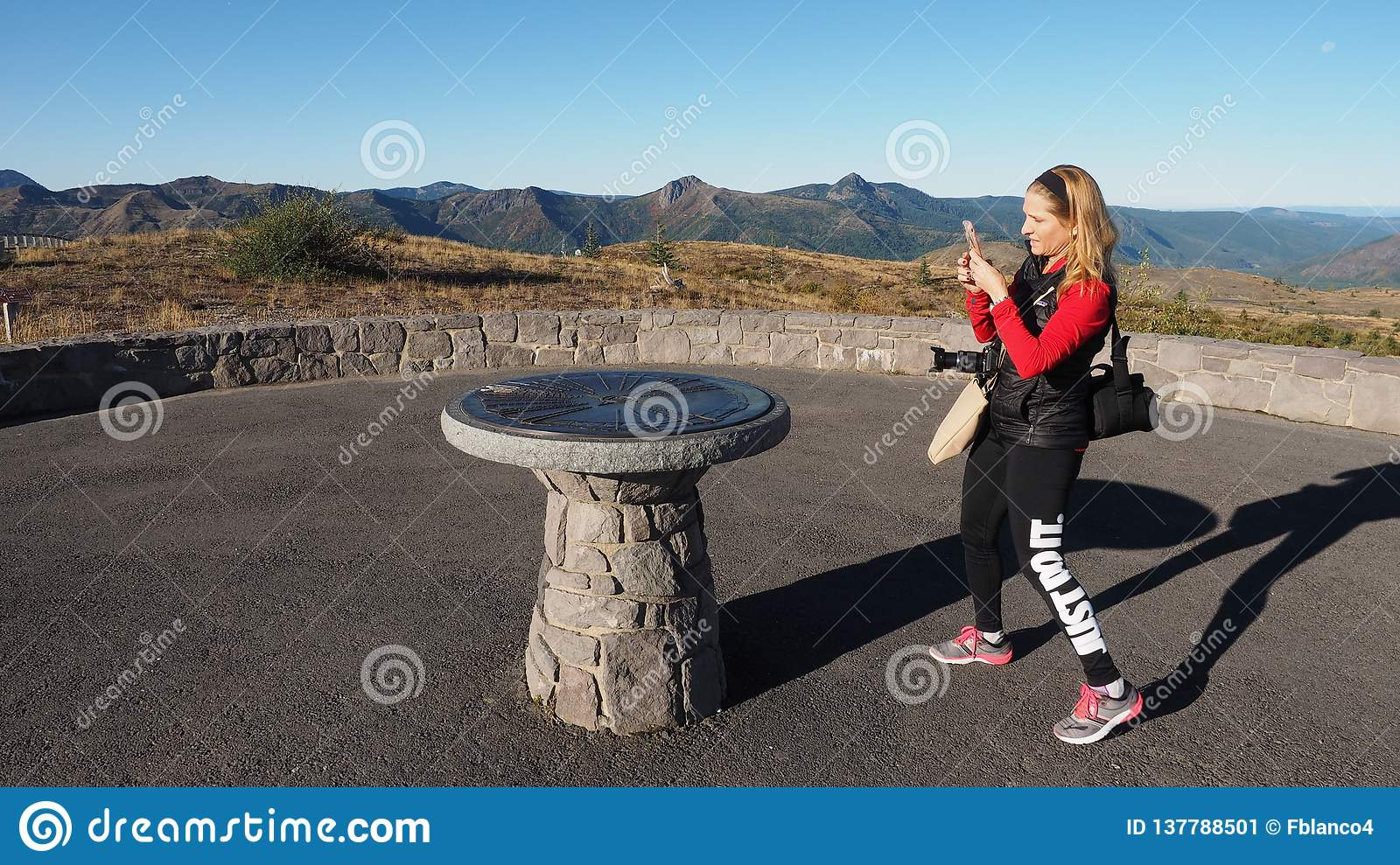 Woman photographing a directional monument at Mount Saint Helens National Volcanic Monument.