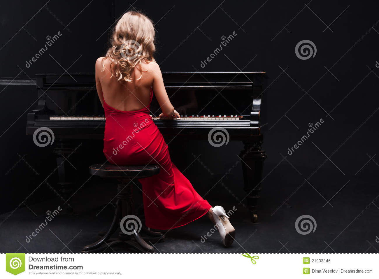 Beautiful young attractive woman in cocktail dress and piano.