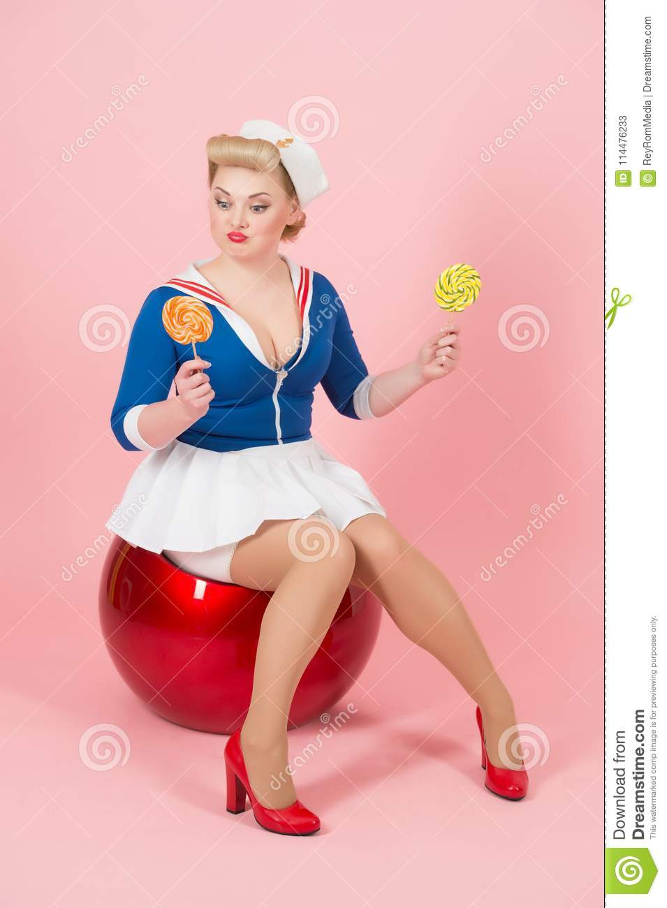 Woman in pin-up style sitting on the red ball with two lollipops