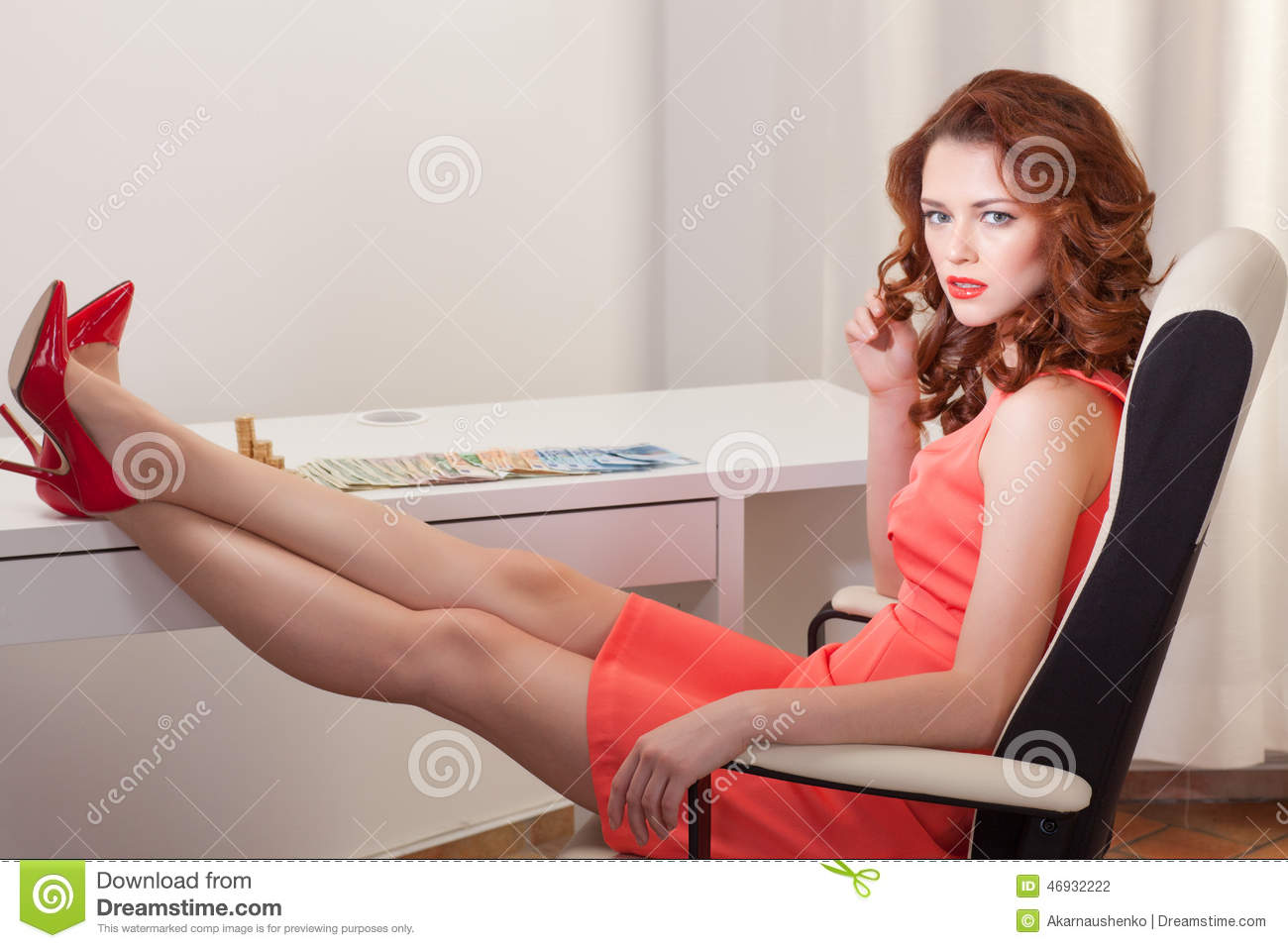 Woman In Pink Dress Sits At A Desk With His Feet Up On The