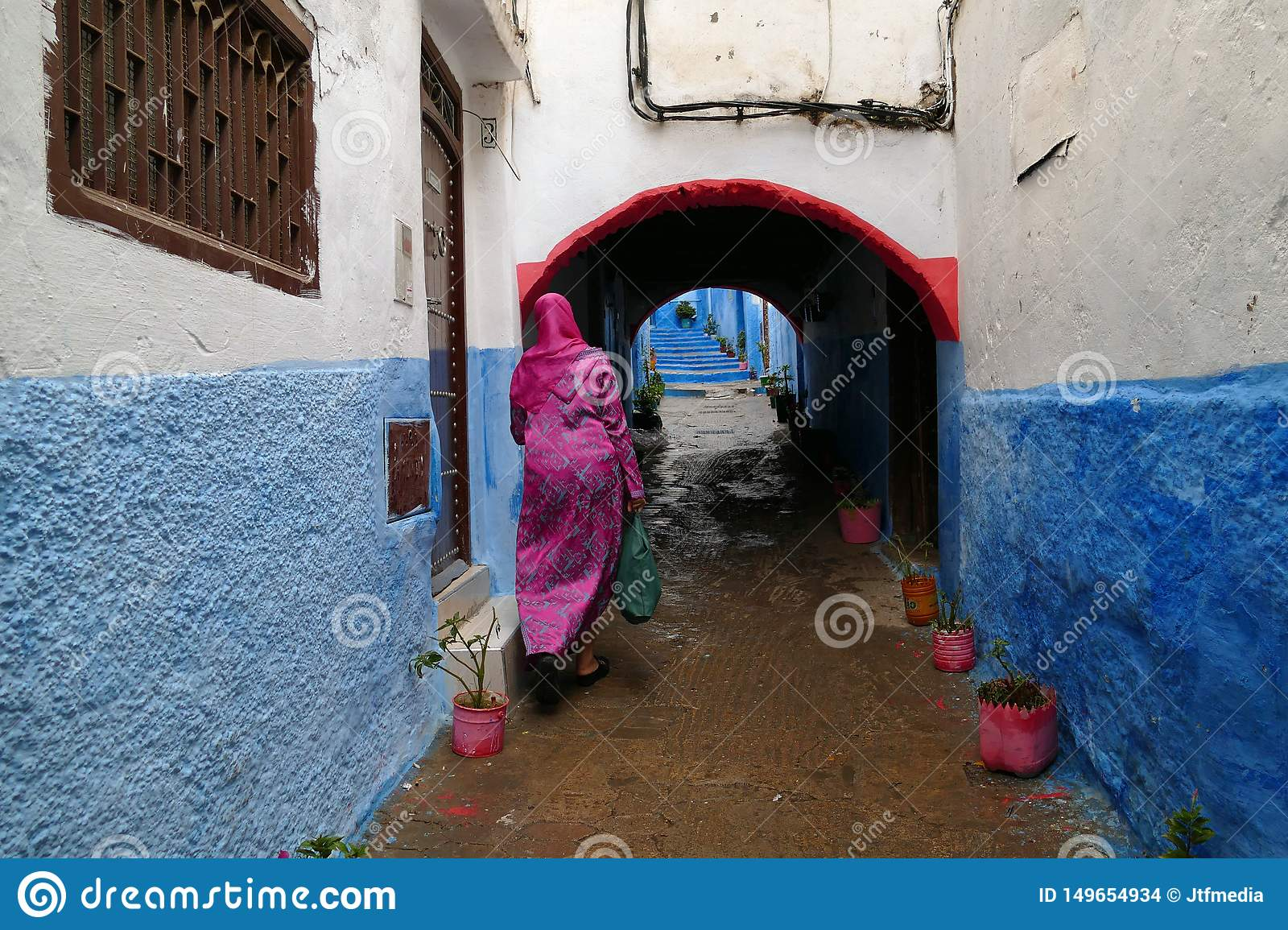 Woman with pink dress walking in a little colorful alley, medina of Tétouan, North of Morocco, Africa