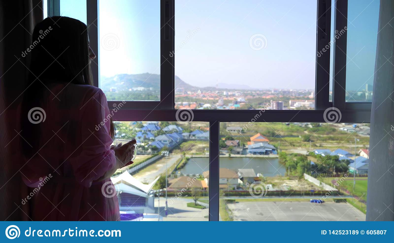 Woman in a pink transparent dressing gown stands and looks out into the panoramic window and drinks coffee. 4k Hua Hin
