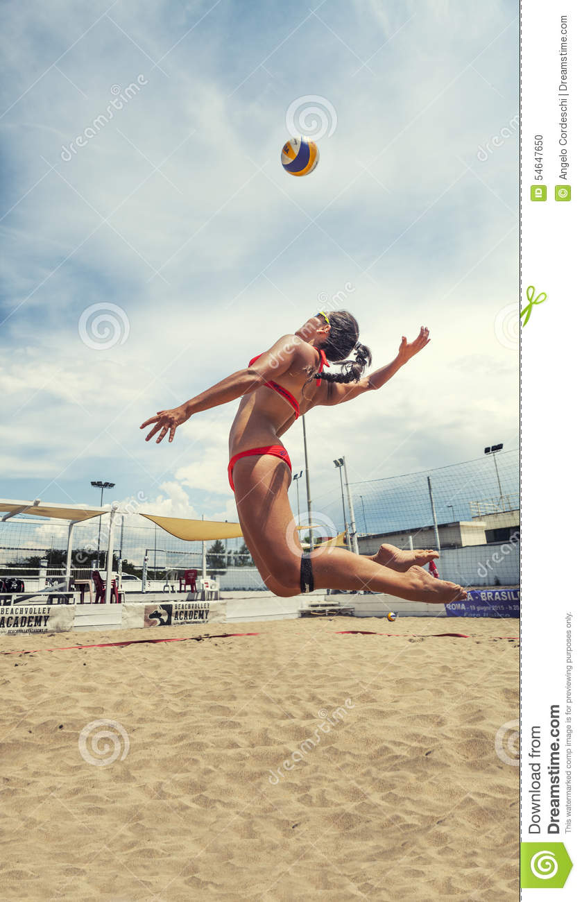 Woman Player Beach Volleyball Jumping To Hit The Ball Spike