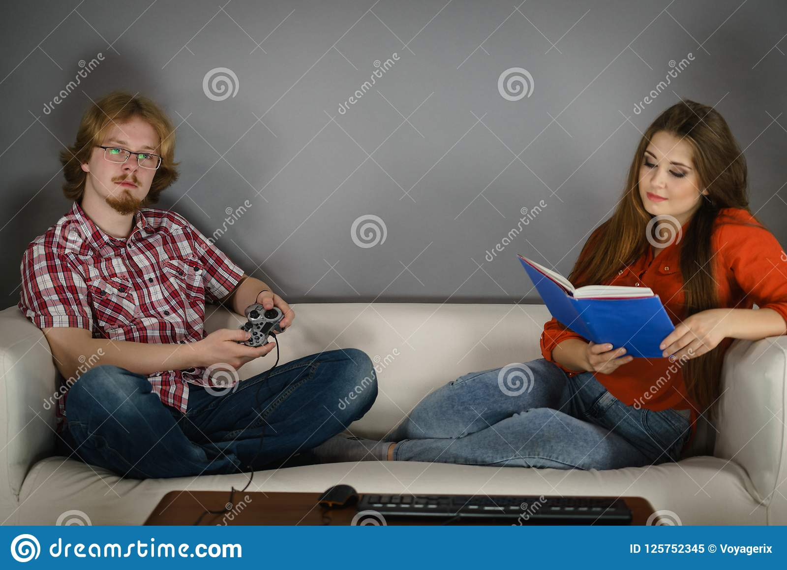 Couple Sitting On Couch Spending Free Time Man Playing Video Games And Women Reading Book