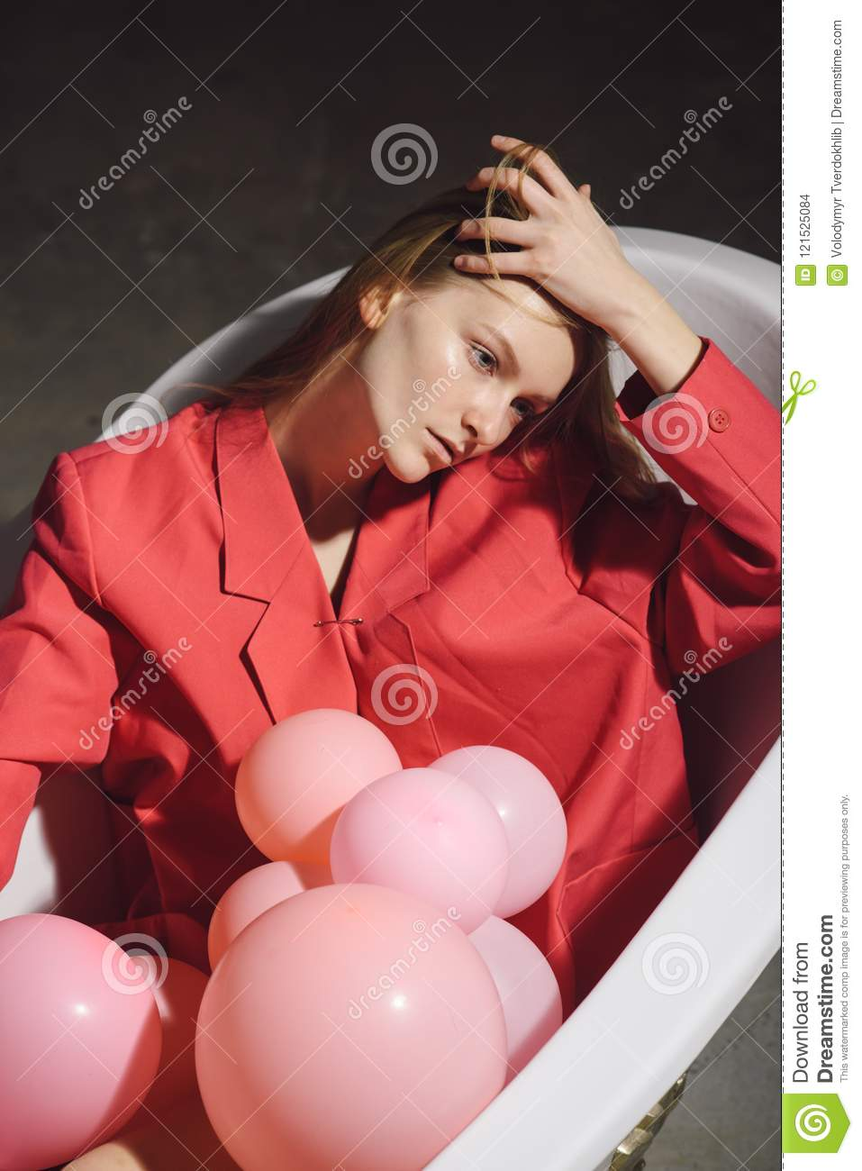 Woman Playing In Her Bath Tub With Pink Colored Balloons