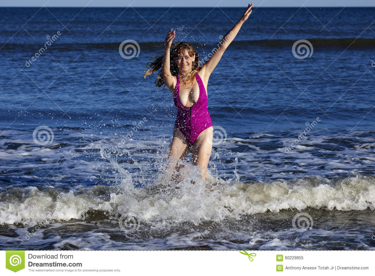 Woman playing and splashing in the ocean