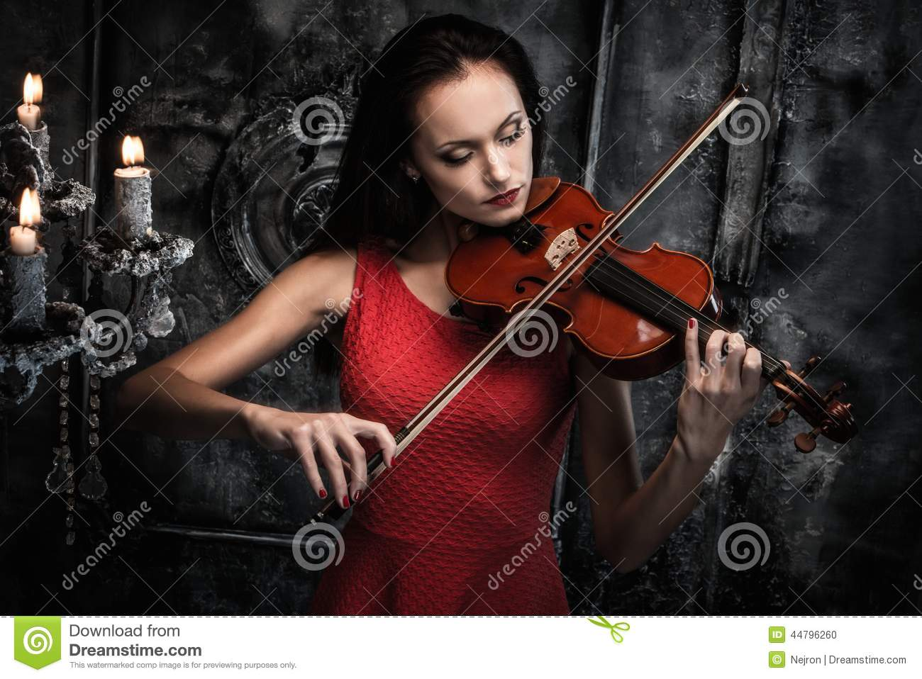 woman playing violin in mystic interior stock photo
