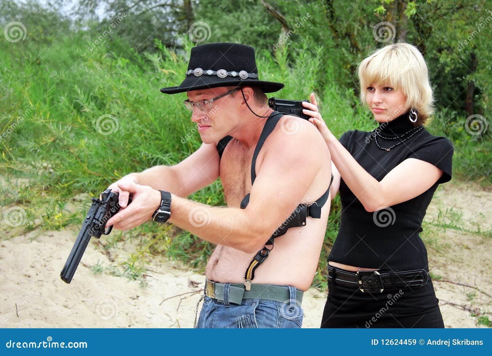 woman pointing gun at shirtless man royalty free stock