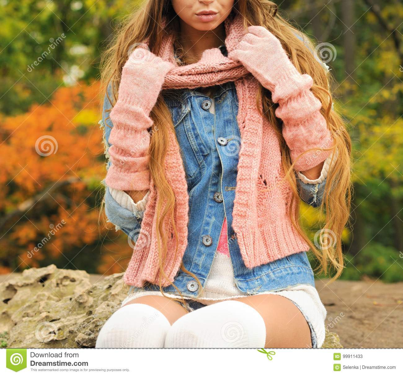 Woman posed outdoor dressed in knitted autumn outfit - warm gloves, scarf and knitted socks
