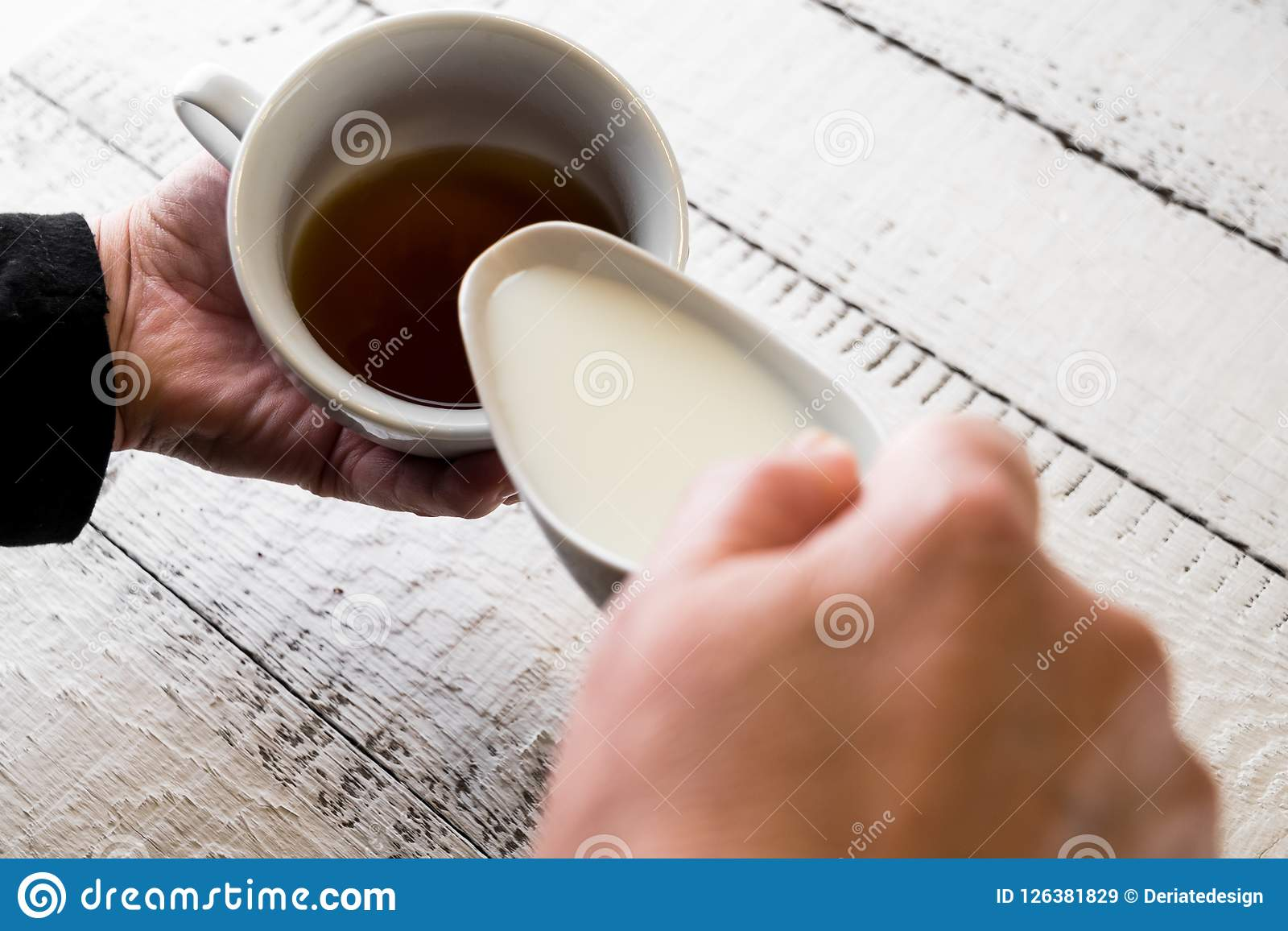 Woman Pouring Milk In To The Cup Of Coffee To Make A ...