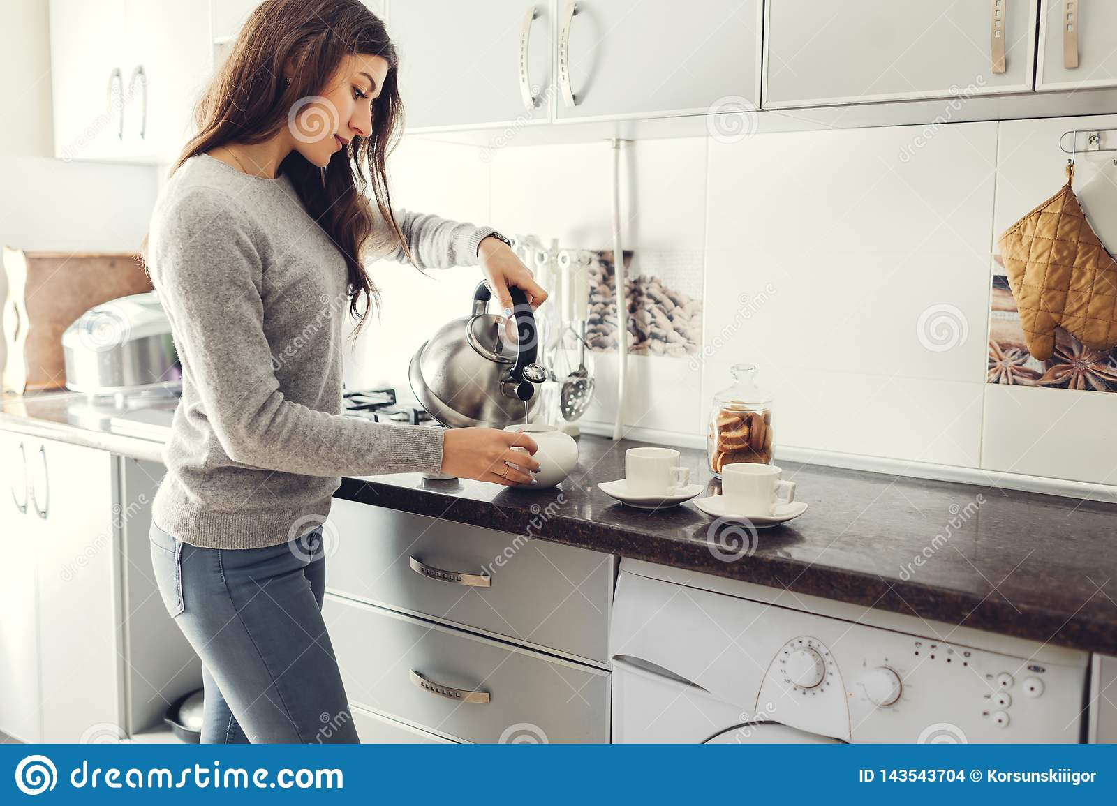 Woman pouring tea into ceramic cup at table